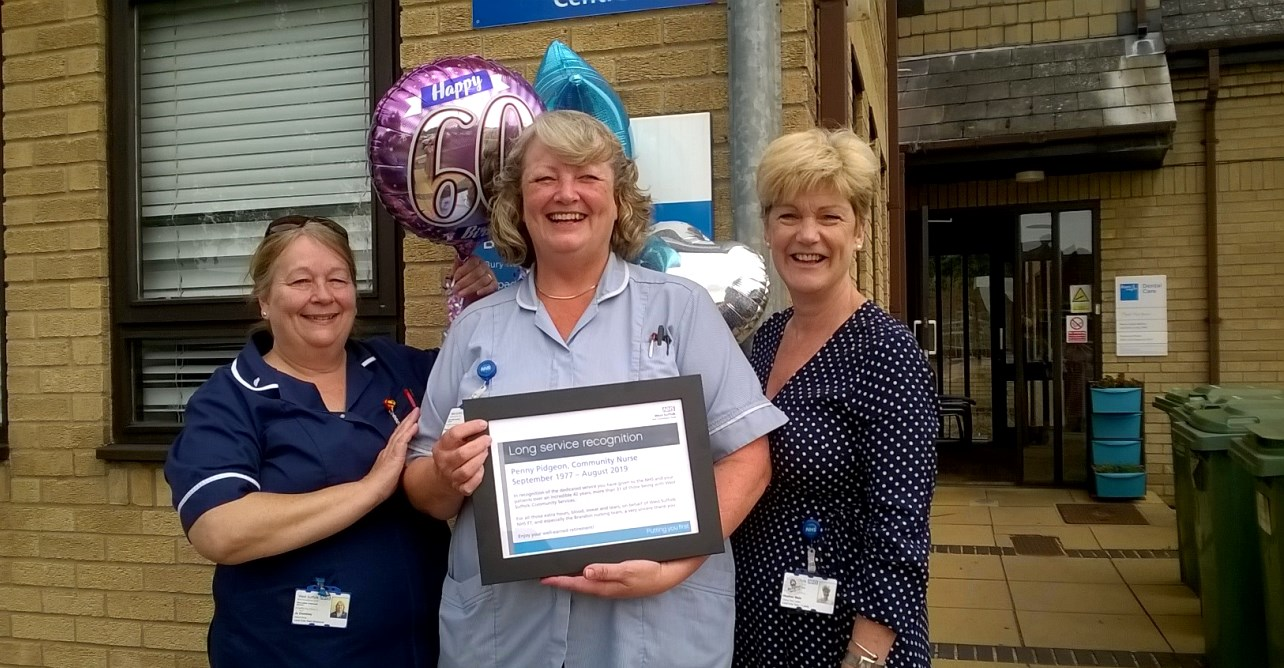 District nursing sister Jo Dominey (left) and team lead Heather Male present Penny Pidgeon (centre) with her long service certificate.
