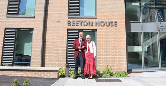 Nigel and his wife Carol are pictured outside one of the new accommodation blocks opened at the hospital in June 2019 which is named in his honour
